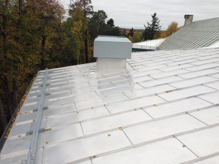 Skivtäckning i aluminium och montering av taksäkerhetsutrustning på skola i Bromma